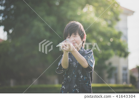 child in kimono playing paper plane outdoors 41643304