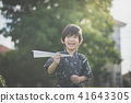 child in kimono playing paper plane outdoors 41643305