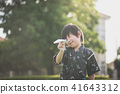 child in kimono playing paper plane outdoors 41643312