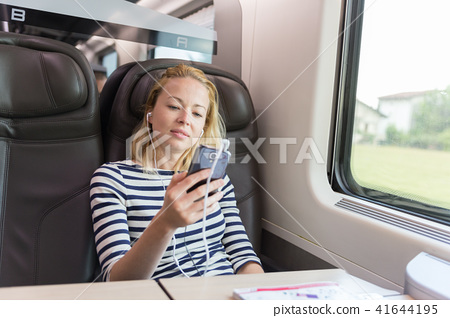 Businesswoman communicating on mobile phone while traveling by train. 41644195
