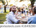 Guests eating at the wedding reception outside in the backyard. 41649280
