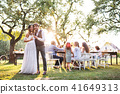 Bride and groom clinking glasses at wedding reception outside in the backyard. 41649313