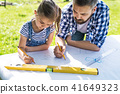 Father with a small daughter outside, planning wooden birdhouse. 41649323