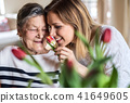 An elderly grandmother with an adult granddaughter at home, smelling flowers. 41649605