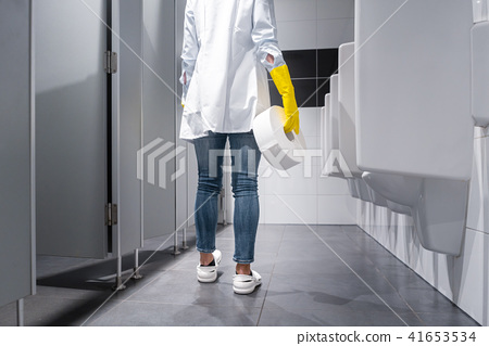 Janitor woman changing paper in public toilet 41653534