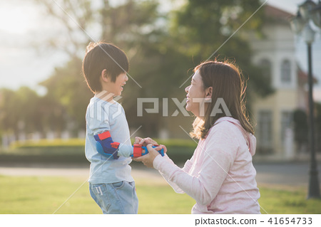mother helping her son putting hand protectors 41654733