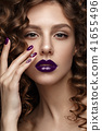 Beautiful girl with evening make-up, purple lips, curls and design manicure nails. beauty face. 41655496
