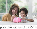 Asian mother and her child putting a coin piggy 41655519