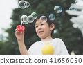 asian child is blowing a soap bubbles 41656050