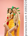 Cute girls in swimsuits posing at studio. Summer portrait caucasian teenagers on pink background. 41660259