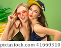 Cute girls in swimsuits posing at studio. Summer portrait caucasian teenagers on green background. 41660310