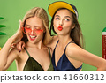 Cute girls in swimsuits posing at studio. Summer portrait caucasian teenagers on green background. 41660312