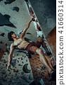 Free climber young man climbing artificial boulder indoors 41660314