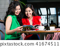 Two young women looking together at a trendy magazine during coffee break 41674511