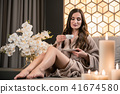 Relaxed young woman drinking herbal tea before spa treatment 41674580