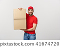 Delivery young man in red uniform holding two empty cardboard boxes isolated on white background 41674720