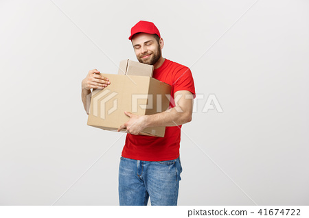 Delivery young man in red uniform huging empty cardboard boxes isolated on white background. Copy 41674722