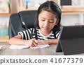 Asian little girl doing homework on wooden table 41677379