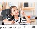 Asian little girl doing homework on wooden table 41677386
