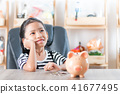 Asian little girl in putting coin in to piggy bank 41677495
