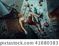 Free climber young man climbing artificial boulder indoors 41680383