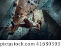 Free climber young man climbing artificial boulder indoors 41680393