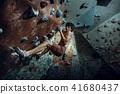 Free climber young man climbing artificial boulder indoors 41680437