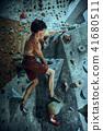 Free climber young man climbing artificial boulder indoors 41680511