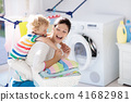 Family in laundry room with washing machine 41682981