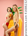 Cute girls in swimsuits posing at studio. Summer portrait caucasian teenagers on pink background. 41686232
