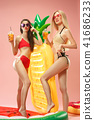 Cute girls in swimsuits posing at studio. Summer portrait caucasian teenagers on pink background. 41686233