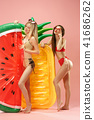 Cute girls in swimsuits posing at studio. Summer portrait caucasian teenagers on pink background. 41686262