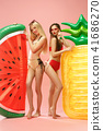 Cute girls in swimsuits posing at studio. Summer portrait caucasian teenagers on pink background. 41686270