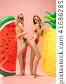 Cute girls in swimsuits posing at studio. Summer portrait caucasian teenagers on pink background. 41686285