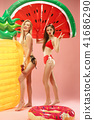Cute girls in swimsuits posing at studio. Summer portrait caucasian teenagers on pink background. 41686290