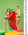 Cute girls in swimsuits posing at studio. Summer portrait caucasian teenagers on green background. 41686308
