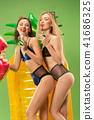 Cute girls in swimsuits posing at studio. Summer portrait caucasian teenagers on green background. 41686325