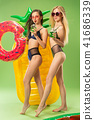 Cute girls in swimsuits posing at studio. Summer portrait caucasian teenagers on green background. 41686339