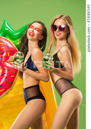 Cute girls in swimsuits posing at studio. Summer portrait caucasian teenagers on green background. 41686340