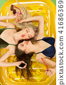 Cute girls in swimsuits posing at studio. Summer portrait caucasian teenagers on matress background. 41686369
