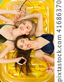 Cute girls in swimsuits posing at studio. Summer portrait caucasian teenagers on matress background. 41686370