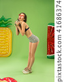 Cute girl in swimsuit posing at studio. Summer portrait caucasian teenager on green background. 41686374