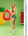 Cute girl in swimsuit posing at studio. Summer portrait caucasian teenager on green background. 41686377
