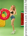 Cute girl in swimsuit posing at studio. Summer portrait caucasian teenager on green background. 41686378