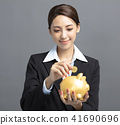 business woman putting money into piggy bank 41690696
