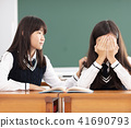 Friend comforting to sad student in classroom 41690793