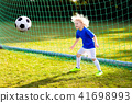 Kids play football. Child at soccer field. 41698993