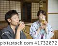 คู่รักในชุดยูกาตะดื่มเบียร์ดราฟที่ด้านข้างของบ้านส่วนตัวเก่า 41732872