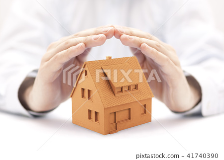 Small orange house protected by hands  41740390