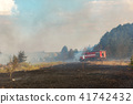 Forest wildfire due to dry windy weather. Fire engine with firefighters handling flame, Blue sky 41742432